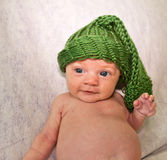 Cute Newborn in Knit Hat. Sweet newborn baby girl wearing a knit stocking hat that makes her look like a cute little elf. Infant is approximately two months old Stock Photo