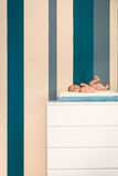 Cute newborn lying on a commode. Cute newborn lying on a white commode Royalty Free Stock Images