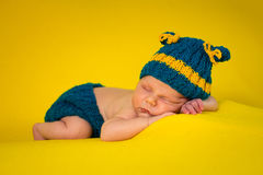 Cute newborn on yellow blanket. 2-weeks baby in costume lying on yellow blanket Royalty Free Stock Image