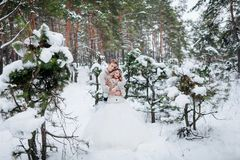 Cute newlyweds beige knitted pullovers hug in snowy forest. Winter wedding. Artwork stock images