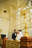 Cute newlyweds are looking each other in the beautiful church. Royalty Free Stock Photos