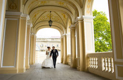 Cute newlyweds are walking under church  arches. Royalty Free Stock Images