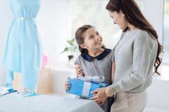 Cute nice girl receiving a present. Thanks mom. Cute nice positive girl smiling and looking at her mom while receiving a pleasant surprise from her Stock Photo