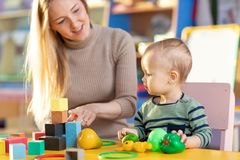 Cute nursery teacher and child toddler playing educational toys in kindergarten royalty free stock photo