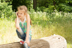 Cute observant little girl on a log Stock Photo