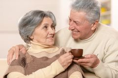 Cute old couple. Drinking coffee at home stock photo