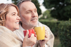 Cute old loving couple in enjoying hot drink Stock Image