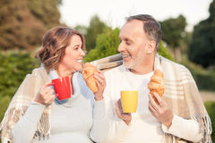 Cute old loving couple is making picnic outdoors Royalty Free Stock Photography