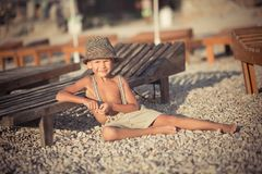 Cute old style boy kid on beach walking posing wearing fancy shorts with gallows and gentleman hat enjoy summer time alone on awes. Ome ocean sea side.Adorable Royalty Free Stock Images