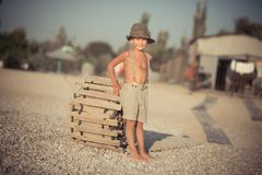 Cute old style boy kid on beach walking posing wearing fancy shorts with gallows and gentleman hat enjoy summer time alone on awes. Ome ocean sea side.Adorable Stock Photography