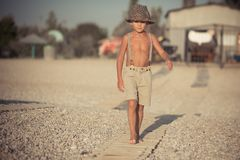 Cute old style boy kid on beach walking posing wearing fancy shorts with gallows and gentleman hat enjoy summer time alone on awes. Ome ocean sea side.Adorable Royalty Free Stock Photos