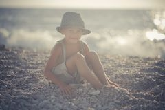 Cute old style boy kid on beach walking posing wearing fancy shorts with gallows and gentleman hat enjoy summer time alone on awes. Ome ocean with anchor Royalty Free Stock Photography
