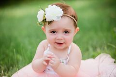 One Year Caucasian Old Girl With Brown Eyes. Cute one year old caucasian girl outside in grass wearing a pink summer dress and floral headband royalty free stock photography