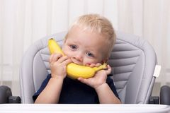Cute one year old toddler eating a banana and sitting in the baby chair. Funny kid with banana smile.  Royalty Free Stock Image