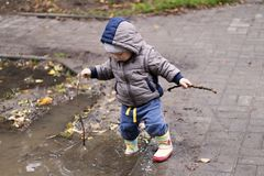 Cute one year toddler dressed in boots and rubber pants jumping in a puddle. Funny kid with children`s happiness. royalty free stock image