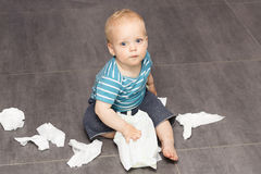 Cute open-eyed baby boy sitting with scattered wipes on the floor.  Stock Images