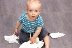 Cute open-eyed toddler sitting with scattered wipes on the floor.  Royalty Free Stock Image