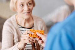 Cute optimistic woman receiving some vitamins. Resisting diseases. Nice feeble elderly lady needing some immune system boosting and having medication prescribed royalty free stock images