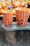 Cute orange buckets stacked and placed on stone bench for Halloween celebrations. Adorable Jack-O-Lantern faces painted on bright orange buckets stacked together stock photography