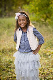 Cute outdoor portrait of a smiling African American little girl. With fall colors in the background Royalty Free Stock Photo