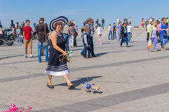 Cute pair - woman with her small dog on the Dnepr river embankment. DNEPROPETROVSK, UKRAINE - SEPTEMBER 12, 2015: Cute pair - woman with her small dog on the royalty free stock photos