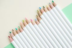 Cute pale color pencils on pastel green and ivory white paper ba. Ckground with copy space using as adult or children coloring or art concept stock images