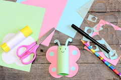 Cute paper butterfly, scissors, marker, glue stick, colored paper set and scraps, ruler, pencil on old wooden table. Kids working Stock Photos