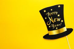 Cute party props accessories on colorful yellow background, happy new year party celebration and holiday concept. Black hat on yellow background stock photography