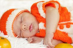 Cute peaceful sleeping newborn baby dressed in a knitted orange. Costume with oranges around of him on white blanket vector illustration