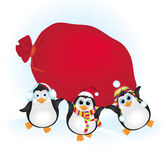 Cute penguins with a bag of gifts Royalty Free Stock Images
