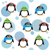 Cute penguins on spotted background. A seamless background of cute cartoon penguins, wearing winter hats, scarves and earmuffs, on blue spotted background Stock Photos