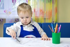 Cute pensive caucasian boy 3 years old drawing with colored pencil in a notebook sitting at a desk in a classroom in a kindergarte royalty free stock photos