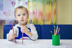 Cute pensive caucasian boy 3 years old drawing with colored pencil in a notebook sitting at a desk in a classroom in a kindergarte royalty free stock photo
