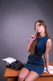 Cute pensive female author. With vintage typewriter Royalty Free Stock Images