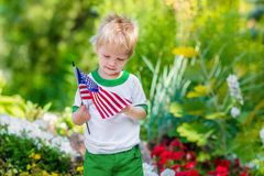 Cute pensive little boy with blond hair holding american flag. And looking at it in sunny park or garden on summer day. Portrait of child on blurred background royalty free stock photos