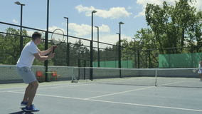 Cute people playing tennis on the tennis court. The camera moves from the right to the left and back. Handsome young woman and attractive cute man are on the stock footage