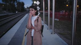 Activity in train. Cute petite woman in brown coat with backpack, student or businesswoman waits for train or bus, worried and preoccupied that she will be late stock footage
