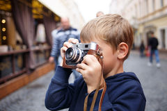 Cute photographer boy holding old film camera. Cute boy holding old film camera and taking a photograph on the street Stock Photography
