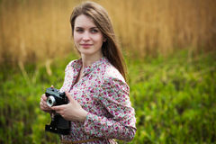 Cute photographer girl is walking on the meadow Royalty Free Stock Images