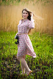 Cute photographer girl is walking on the meadow Royalty Free Stock Photo