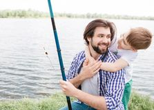 Cute picture of bearded dad and his small son spending time together. Boy is hugging his dad while man is smiling and. Cute picture of bearded dad and his small Royalty Free Stock Images