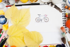 Cute pictured bicycle with autumn leaves flat lay