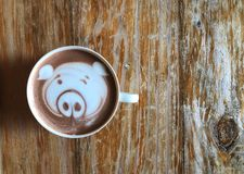 Cute pig face latte art coffee in white cup on wooden table stock photos