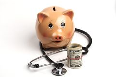 Piggy Bank Health Care. Cute Piggy Bank With Black Stethoscope and Dollar Banknotes Roll Isolated on White Background royalty free stock images