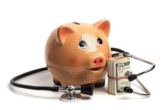 Piggy Bank Health Finance. Cute Piggy Bank With Black Stethoscope and Dollar Banknotes Roll Isolated on White Background royalty free stock photo