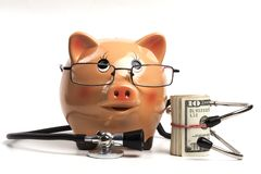 Glasses on Piggy Bank. Cute Piggy Bank With Black Stethoscope and Dollars Roll Banknotes Isolated on White Background stock image