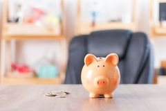 Cute piggy bank and coins on wooden table with copy space Royalty Free Stock Photos