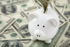 Cute Piggy Bank on heaps of cash Royalty Free Stock Photos