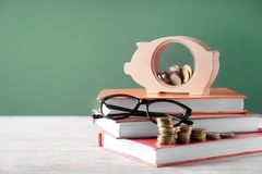 Free Cute Piggy Bank With Books And Coins On Table Against Color Background. Concept Of Education Royalty Free Stock Photo - 151280435