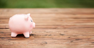 Cute Piggy Bank on the Wooden Table Royalty Free Stock Photos